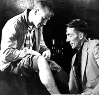 Yankees' scout Tom Greenwade examines Mickey Mantle's knee. Mickey points to the scar from his injury in the 1951 World Series.